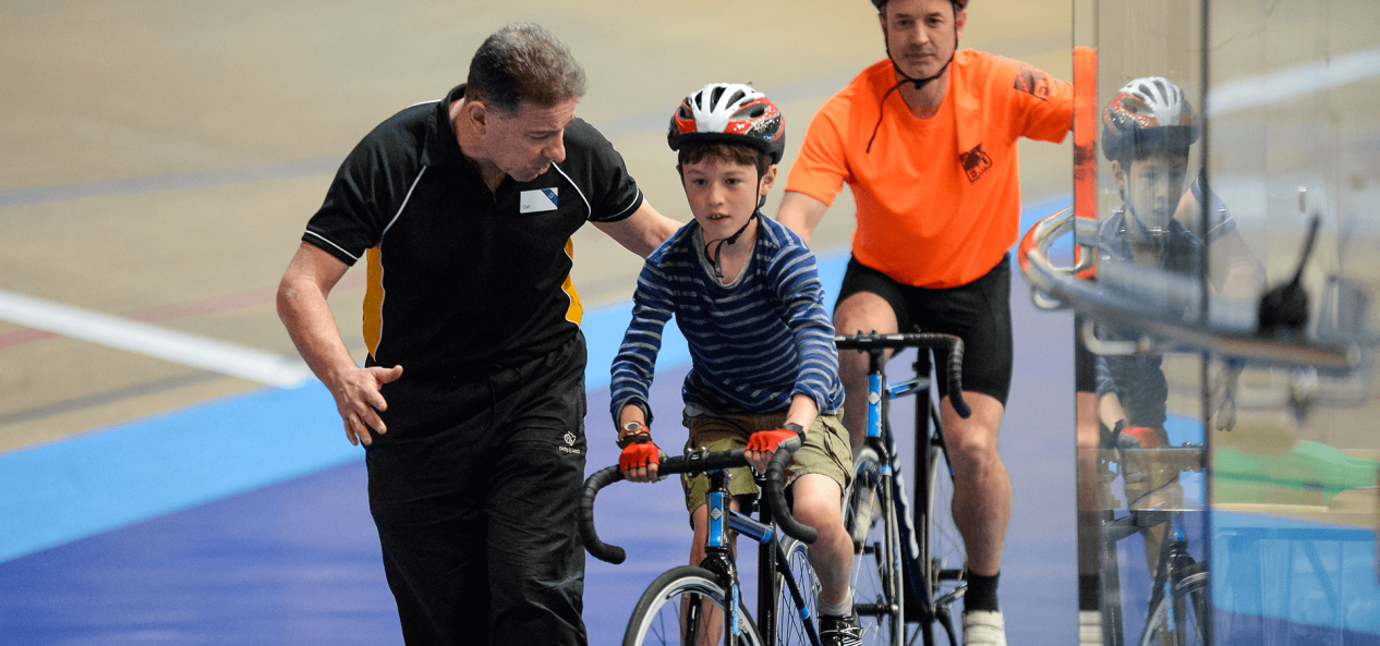Coach helping young boy cycling on velodrome