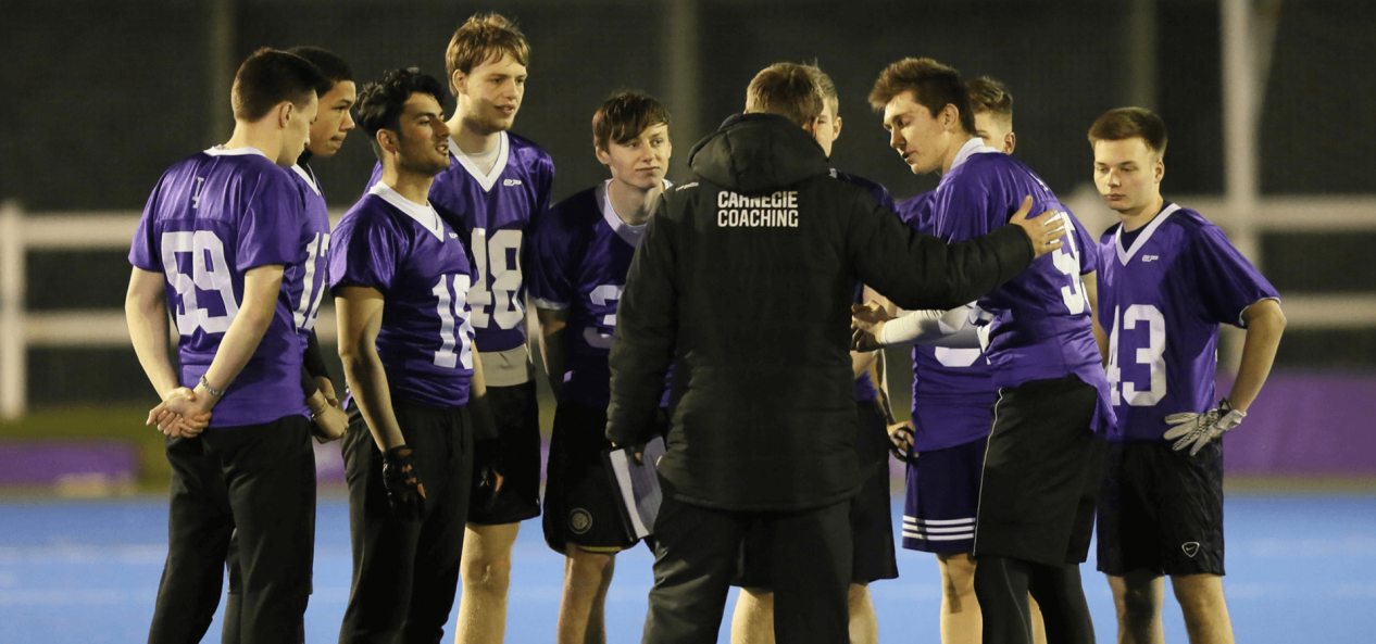 Coach talking to football players on pitch