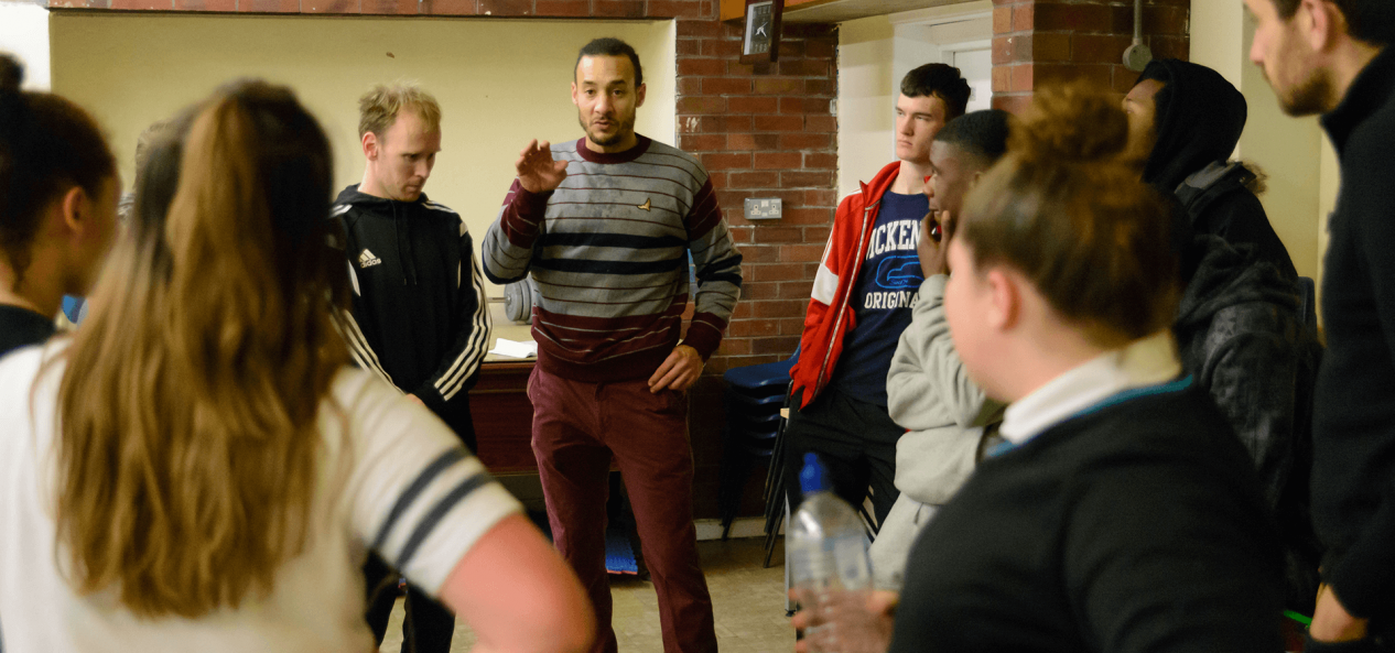 Coach talking to young people in rounds