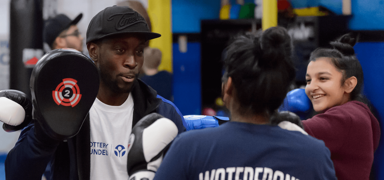 Coach teaching young girl boxing