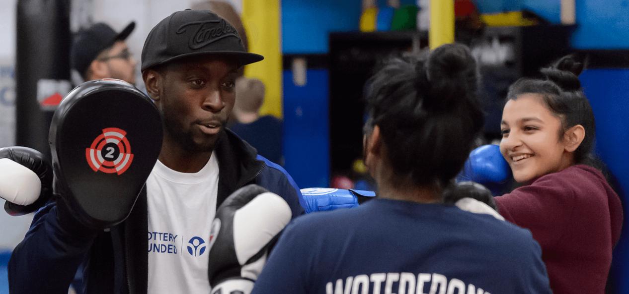 Coach teaching young girl boxing