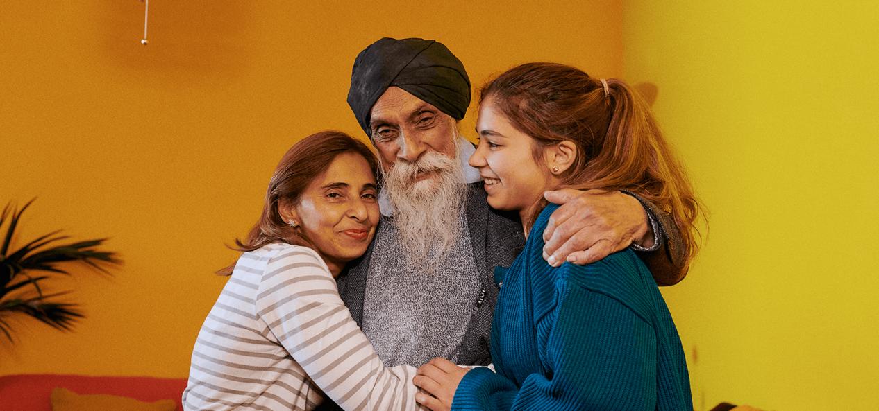 Daughter and granddaughter hugging grandfather