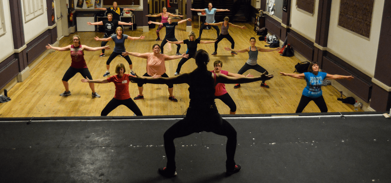 instructor teaching stretches in an exercise class for women