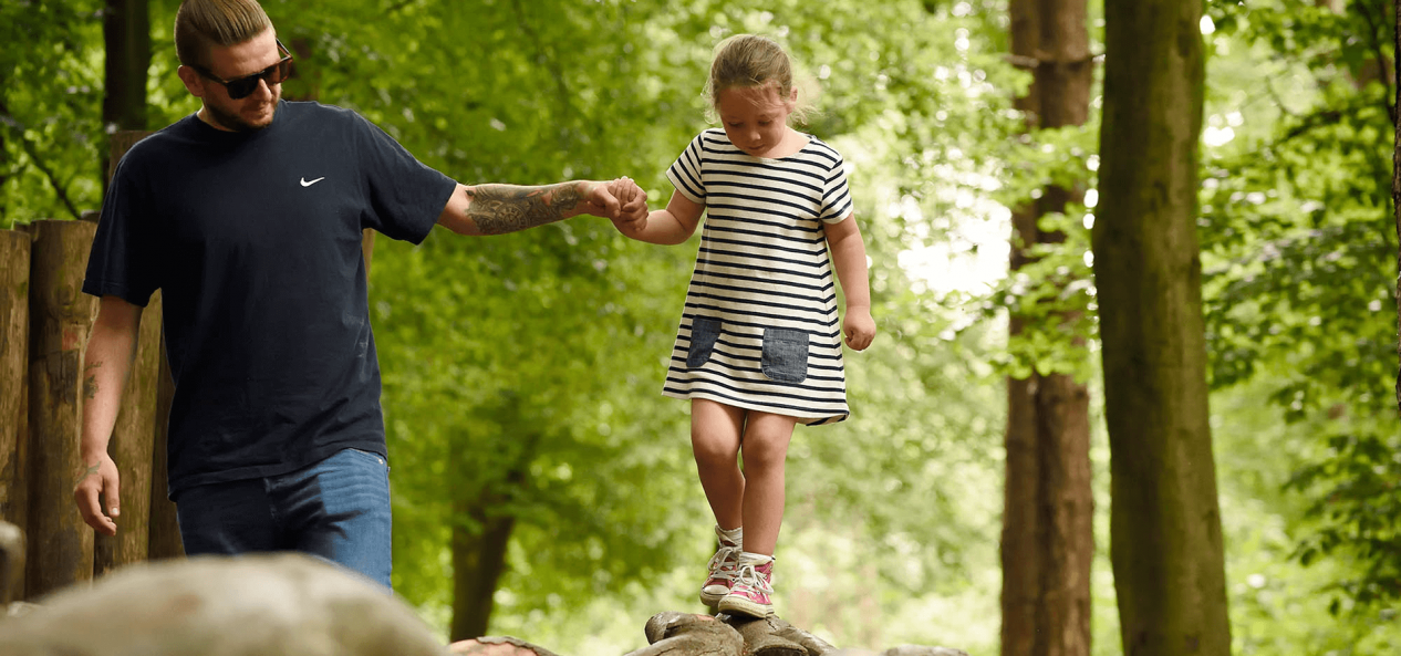 Father holding daughter's hand as she's walking