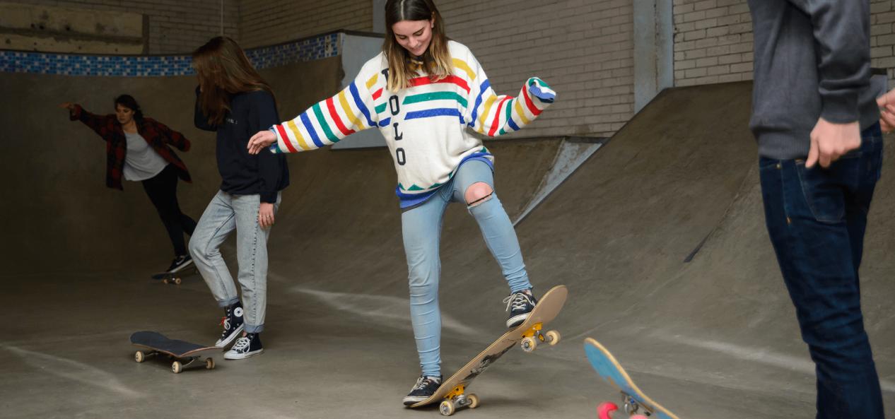 Girl learning to ride skate board in skate park