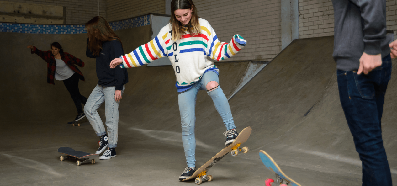 Girl learning to ride skate board in skate park