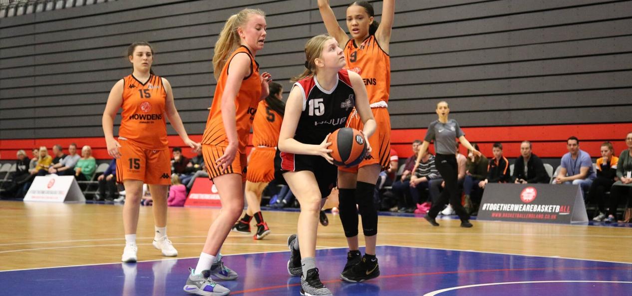 Girls guarding shooter during basketball game
