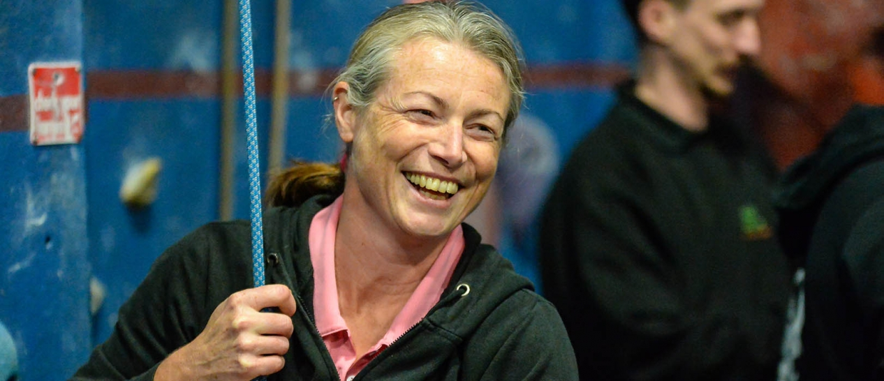 A woman smiles while holding a rope at the foot of an indoor climbing wall