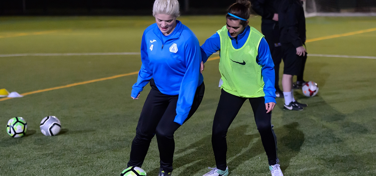 Two girls playing football on a 3G pitch