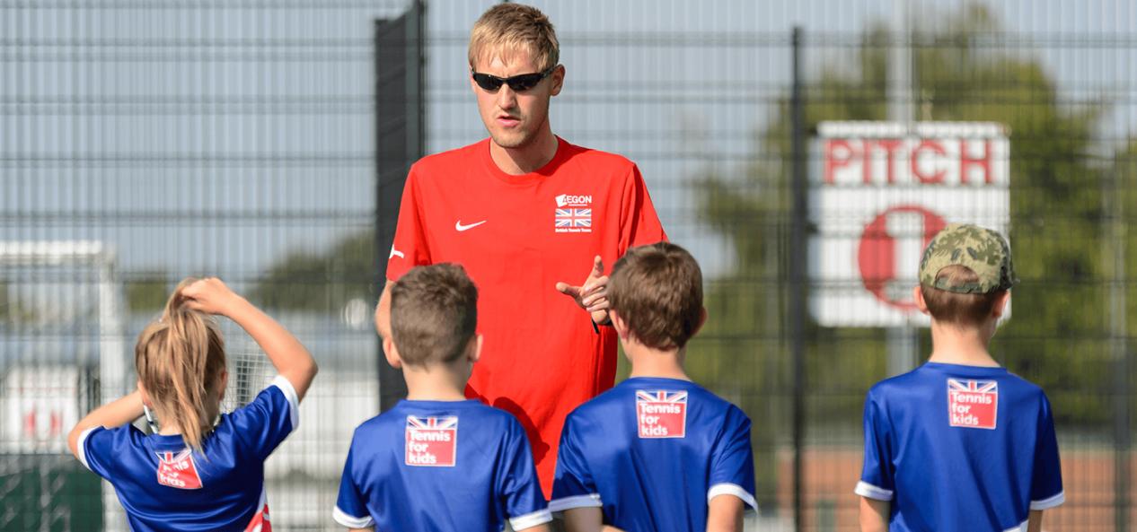Man coaching young children for tennis game