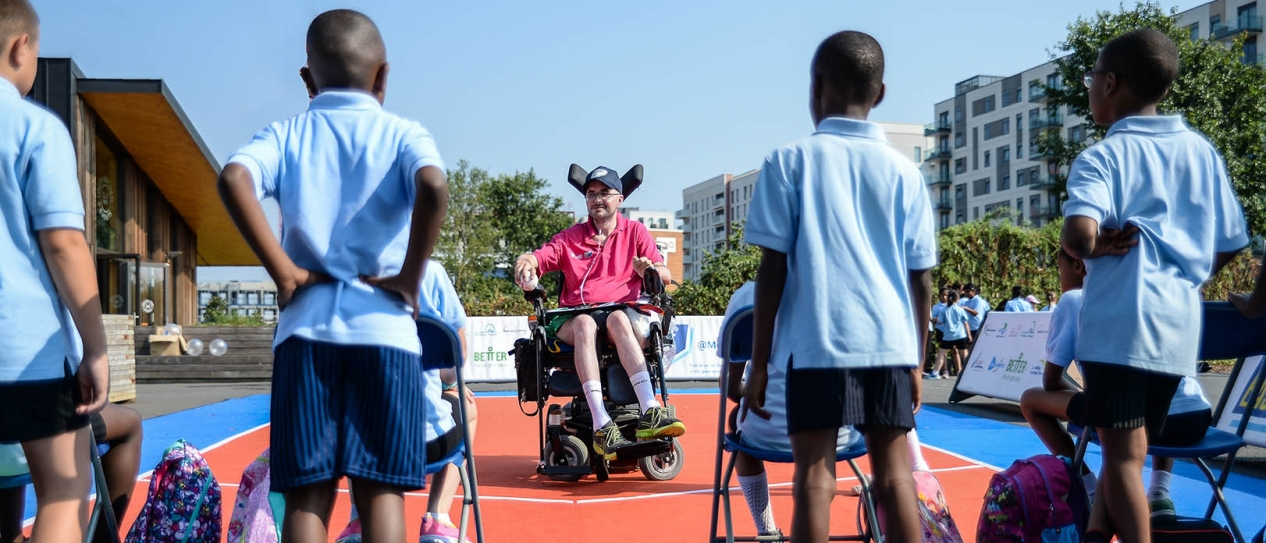 A group of children listen to a coach in a wheelchair