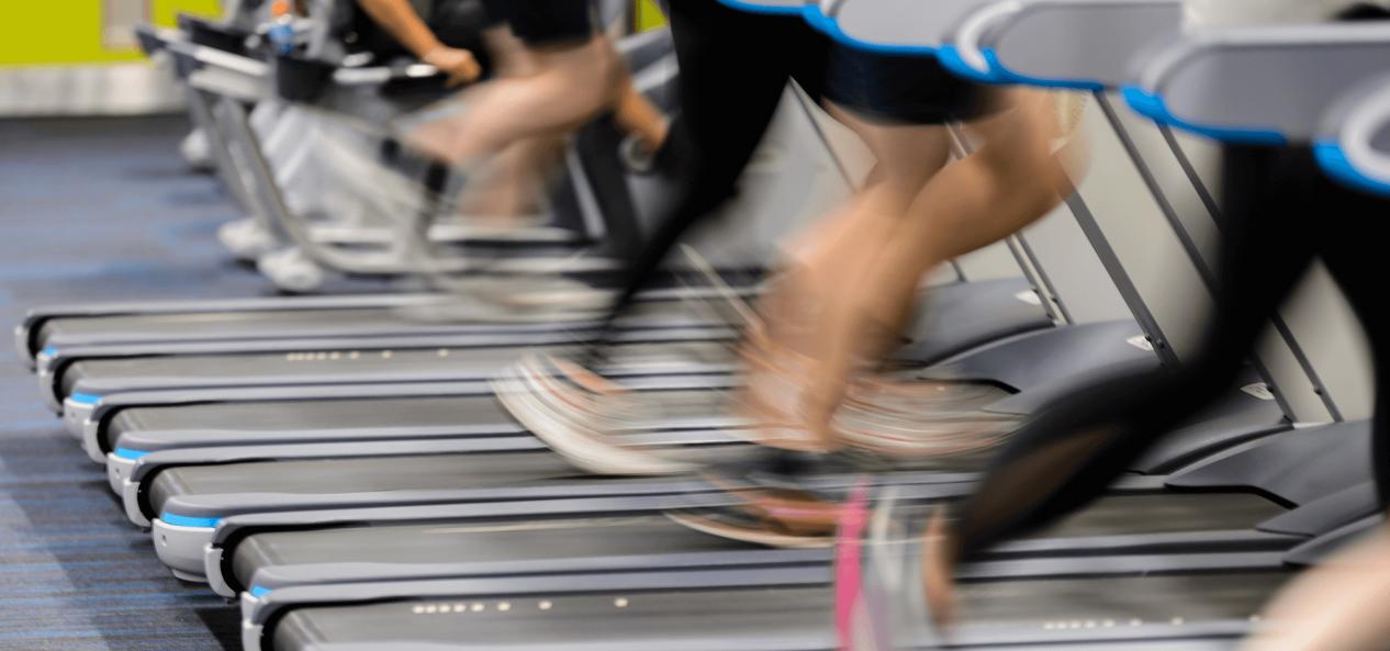 人们在健身房的跑步机上跑步
