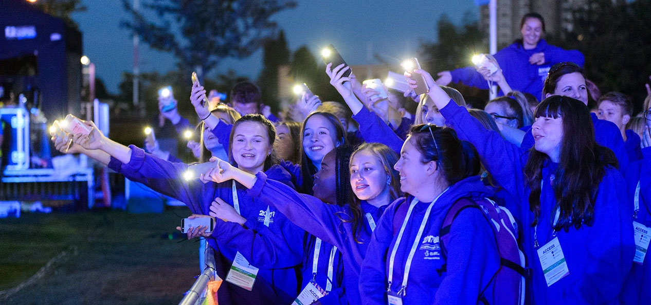 A group of schoolchildren using their phones as torches at the 2017 School Games