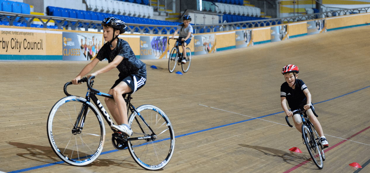 Three boys cycling on velodrome