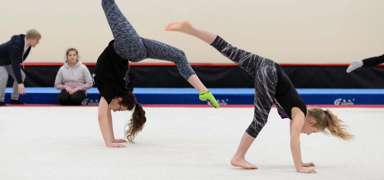 Two girls doing gymnastics in sports hall