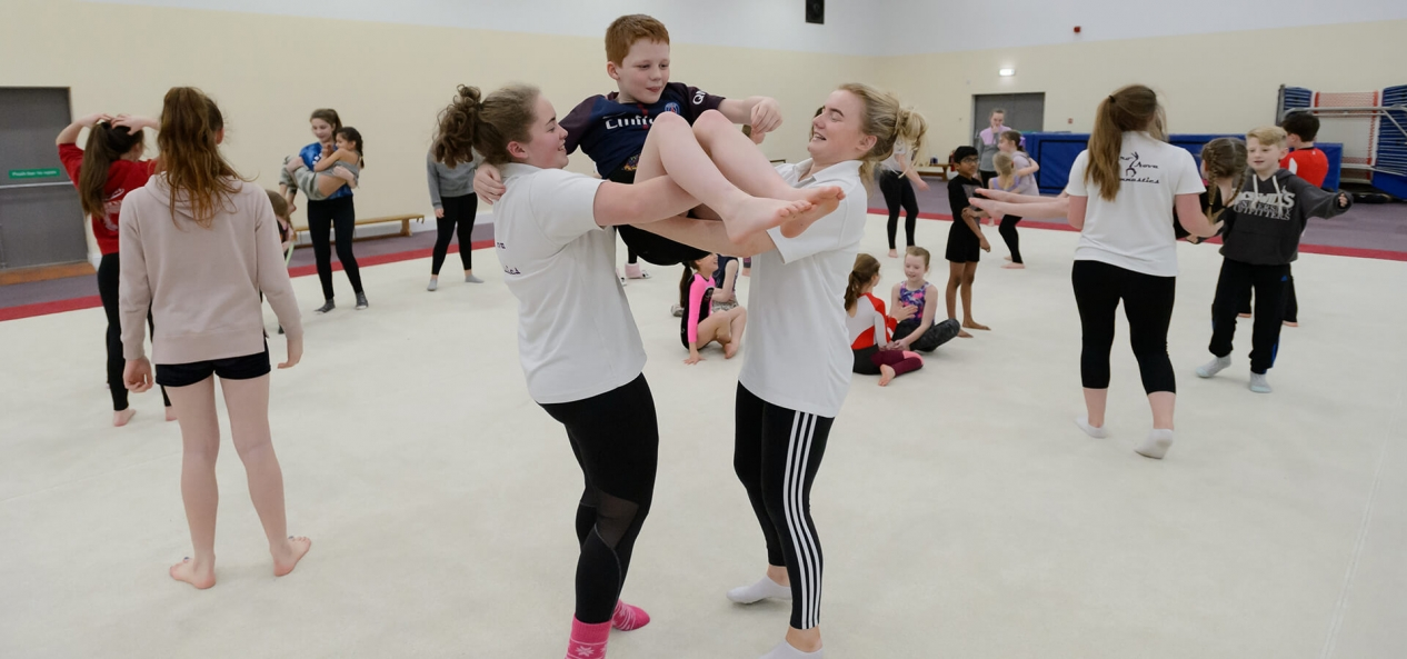 Two girls lifting young boy in sports hall