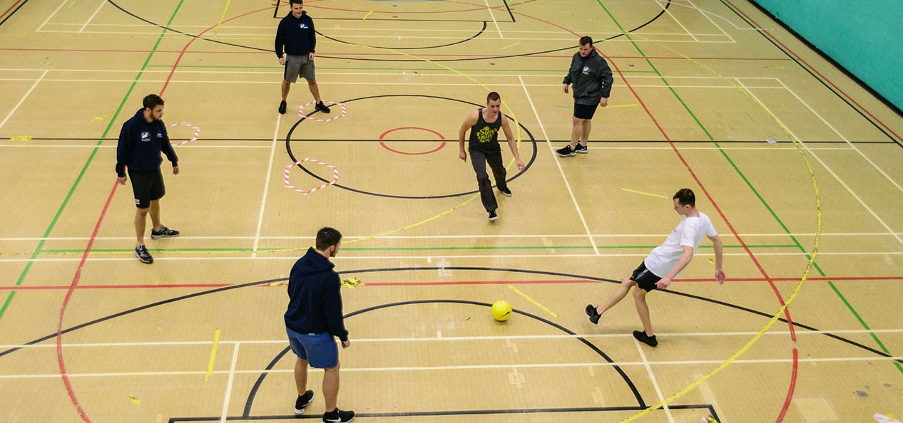 Overhead shot of a group of group of men kicking a football around a sports hall