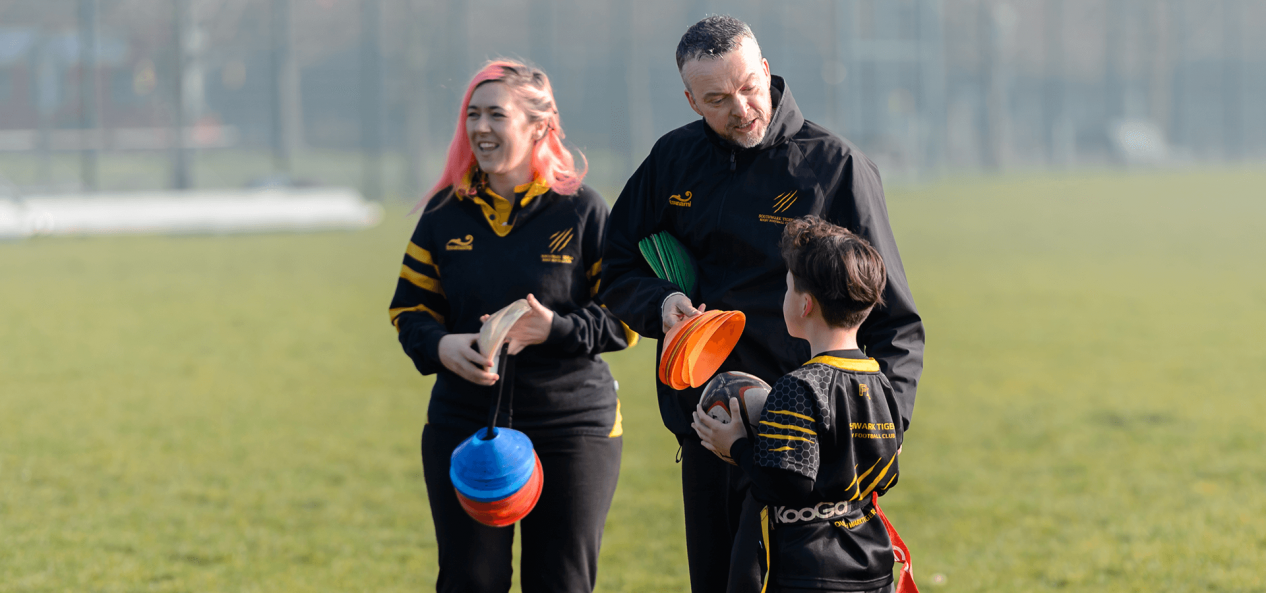 Volunteering rugby coaches helping out