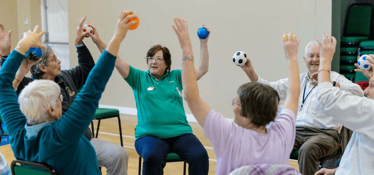 A class takes part in sitting exercises with mini footballs