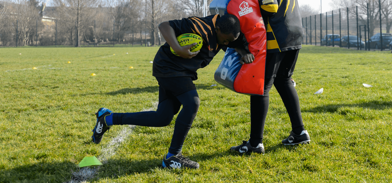 Young boy practicing american football tackle using cushion