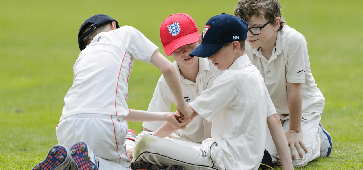 Young boys helping each other during cricket