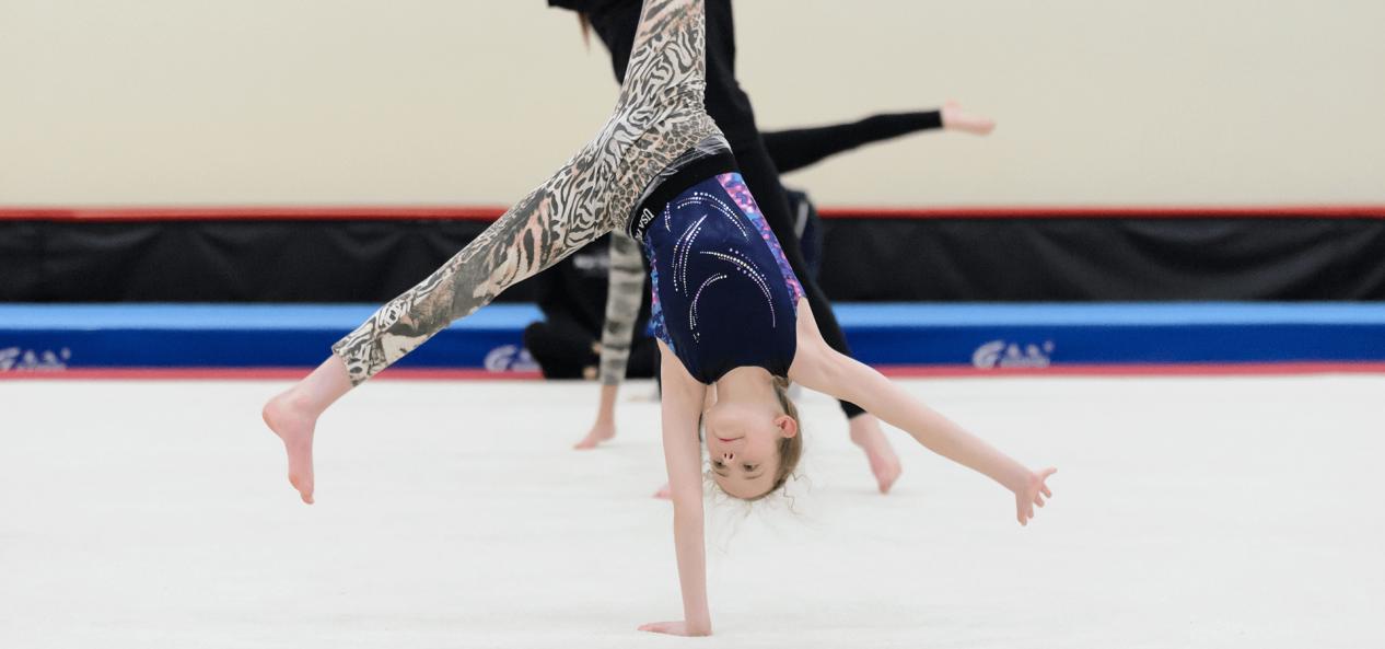 Young girl doing hand stand gymnastics