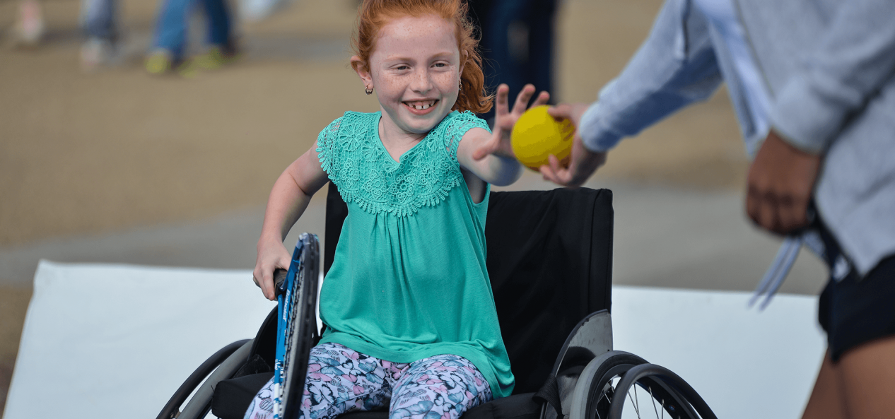 Young girl in wheelchair receiving ball