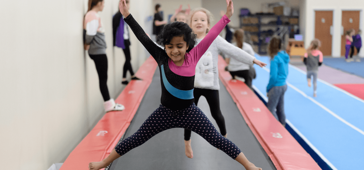 Young girls jumping on long trampoline