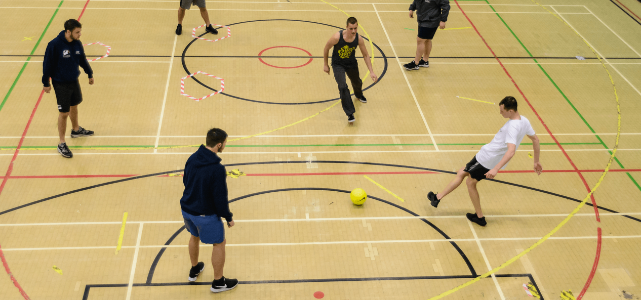 Young men playing football in sports hall