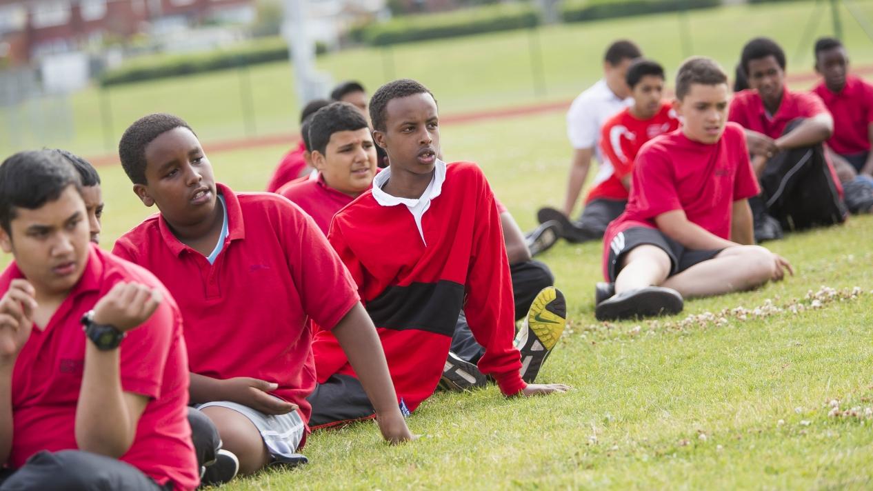Athletics boys sitting down on the grass