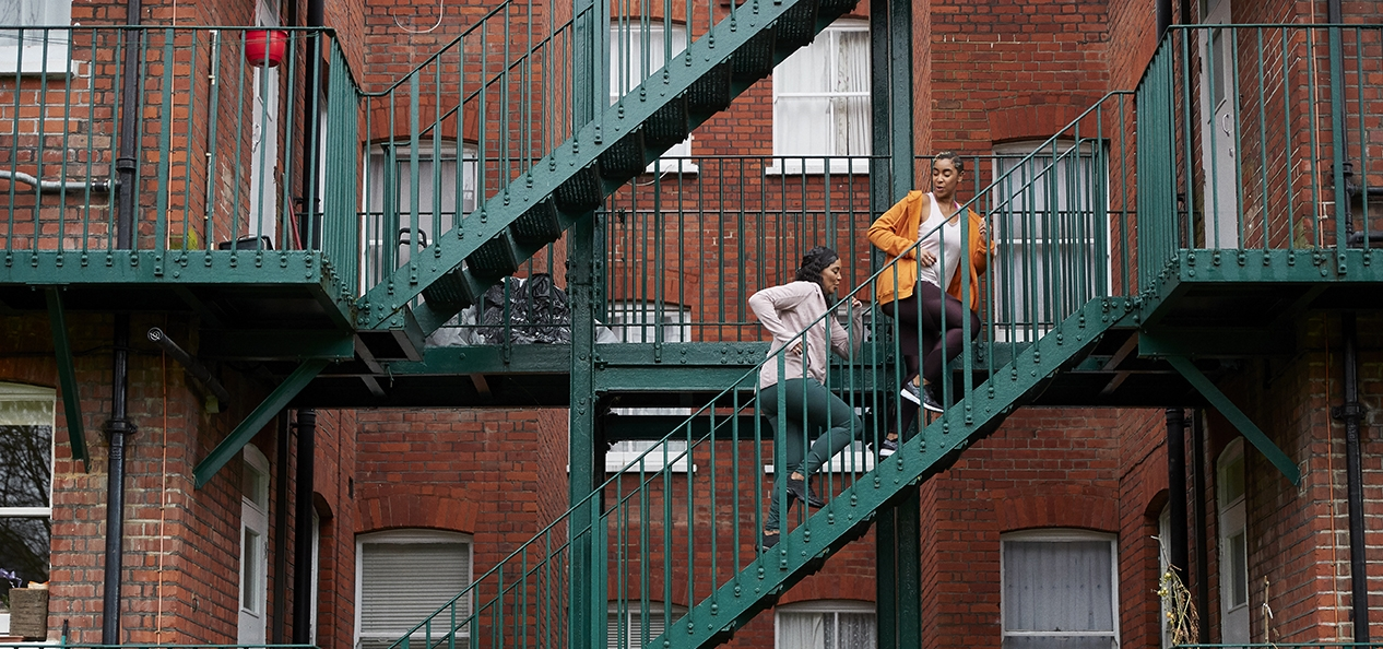 Two women running up stairs within a housing complex.