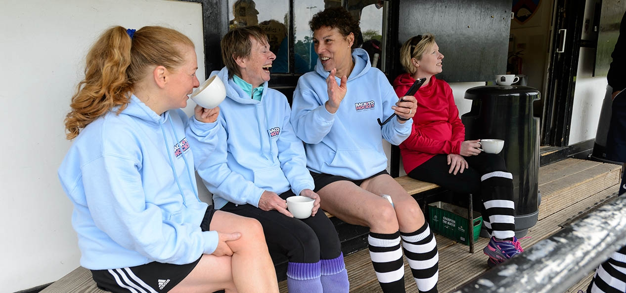 A group of women having a chat during a break in a game of hockey.