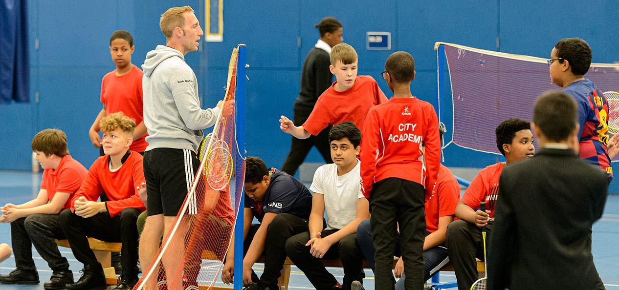 A PE teacher and children inside a sports hall.