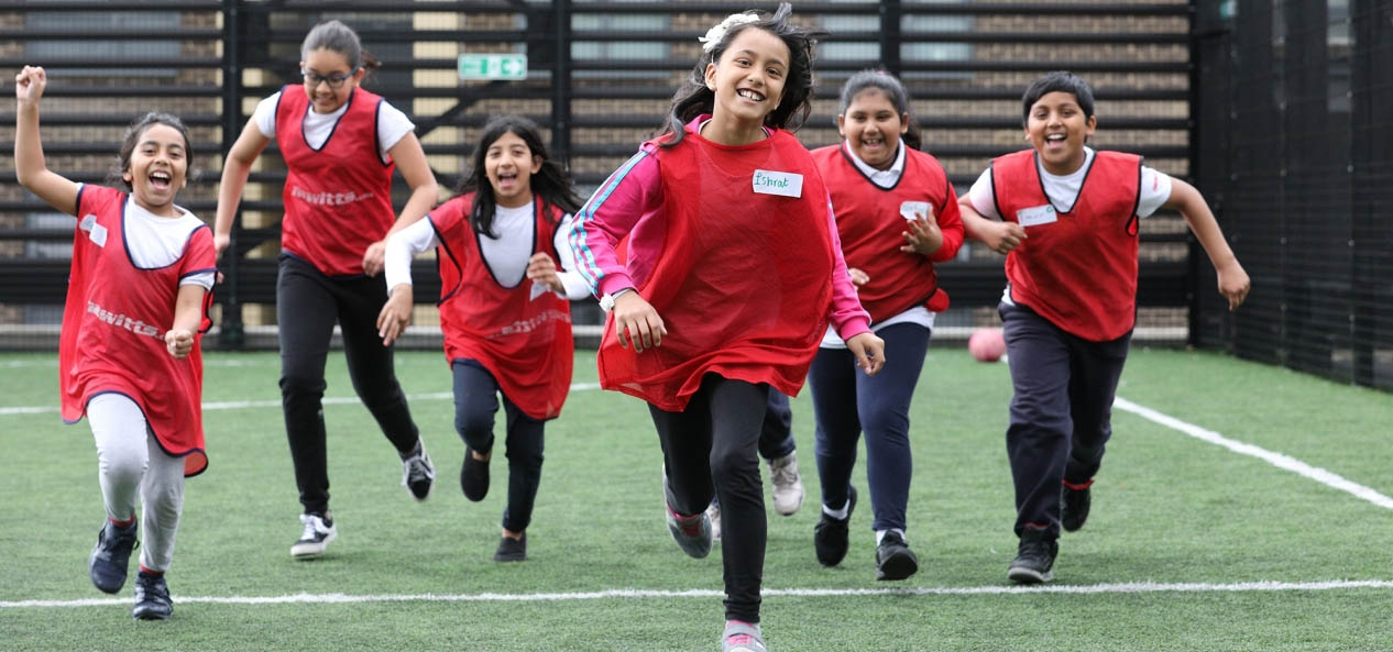 A group of smiling children running towards the camera.