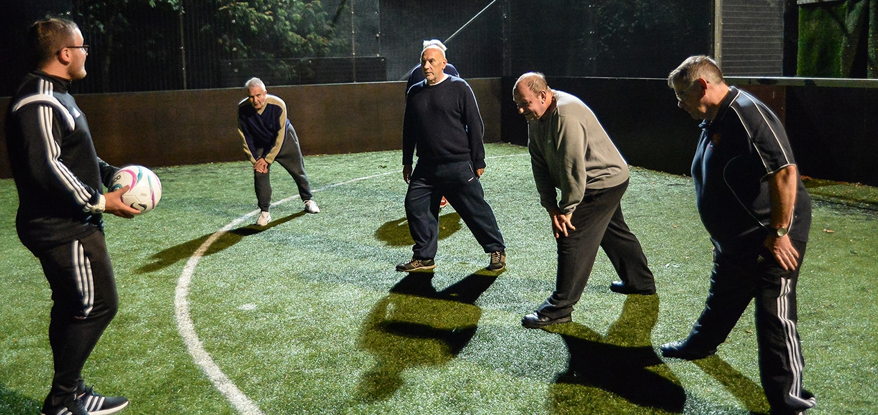 A group of men doing stretches at a walking football session.