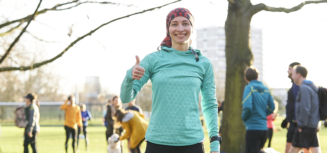 A woman gives a thumbs up to the camera after completing a parkrun