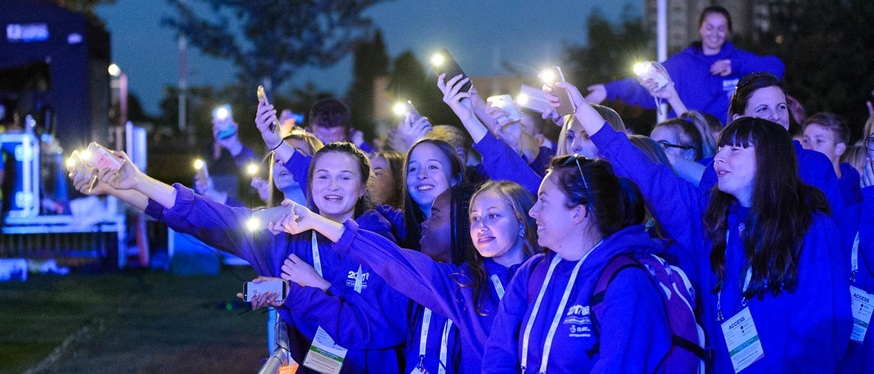 A group of School Games participants holding their mobile phones in the air with the torch lights on.