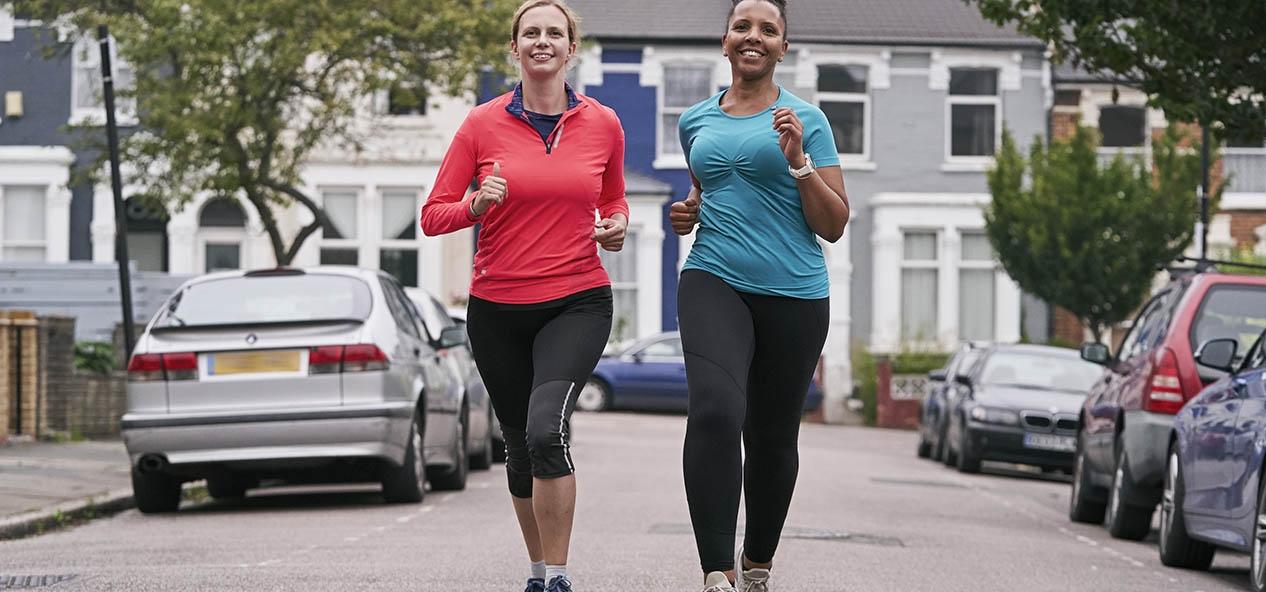 Two women running along a road
