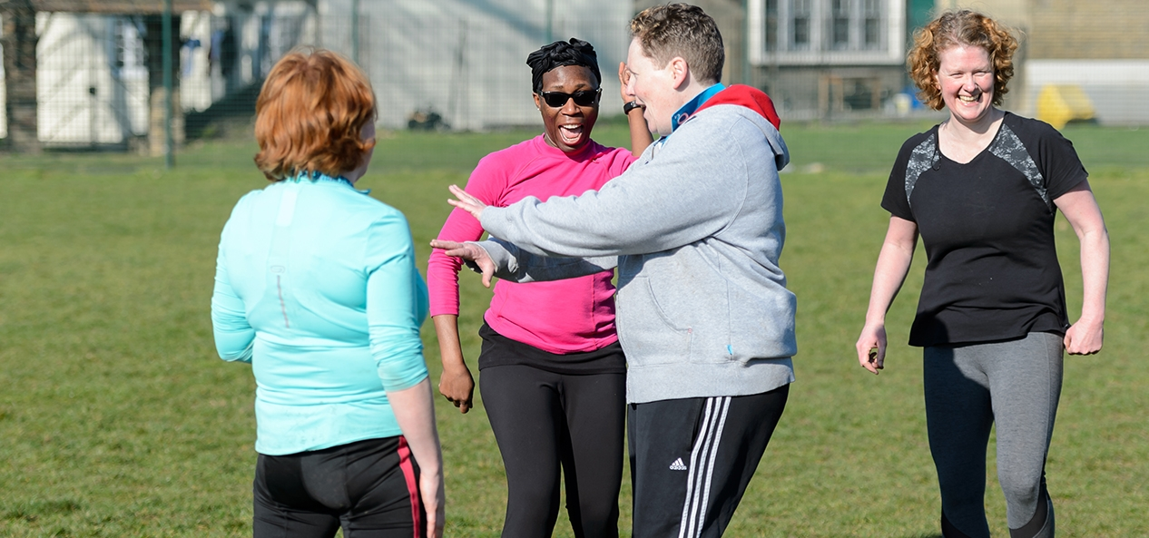 A group of people chatting and smiling on a rugby field.