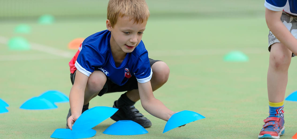 A boy laying out cones on the ground before the start of a tennis session.