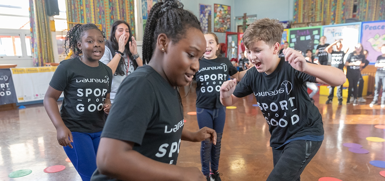 Children wearing Laureus sport for good t-shirts play in a school hall
