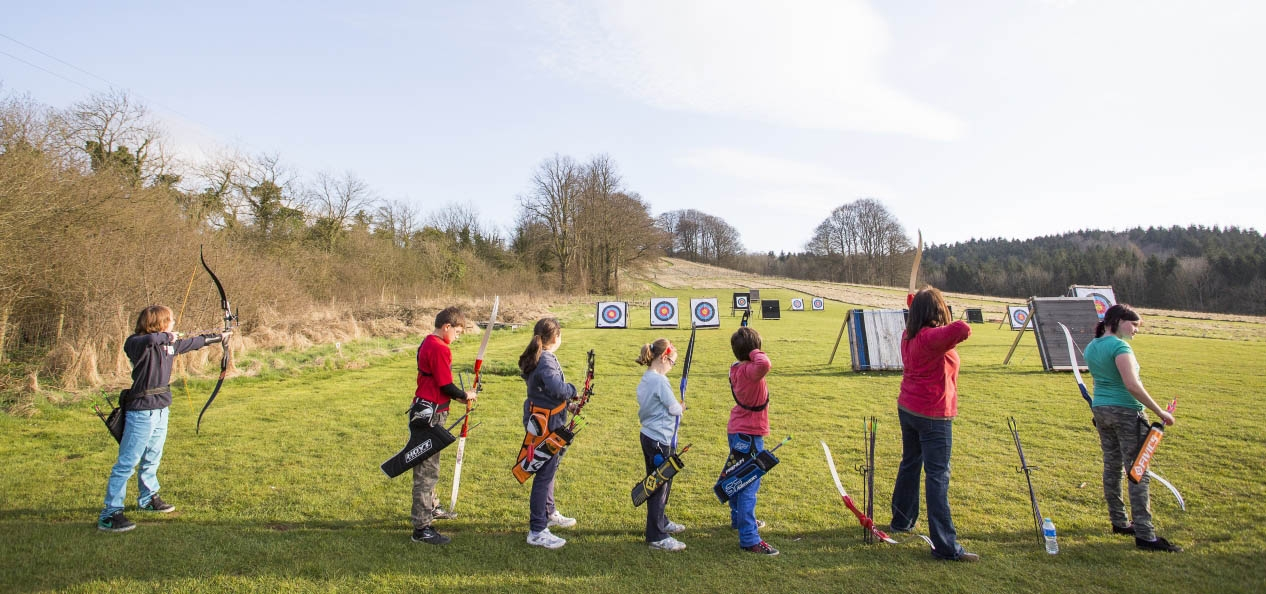 A group of young people aiming their arrows during an archery session.