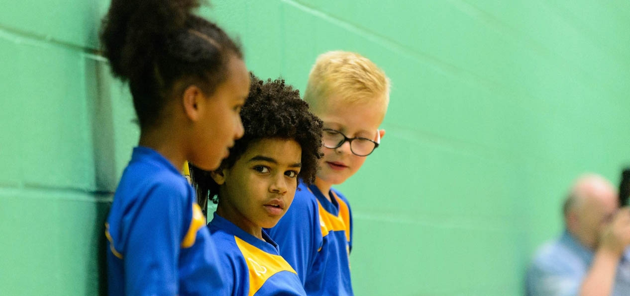 A group of children in a sports hall.