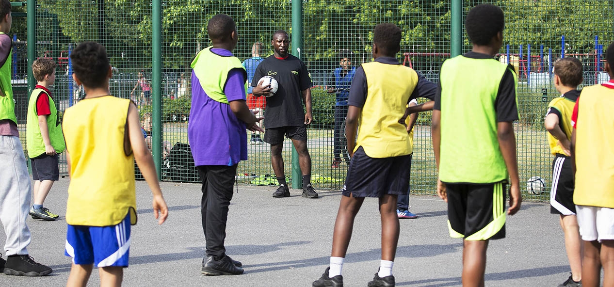 A group of boys listen to an instructor during a football session in a playground