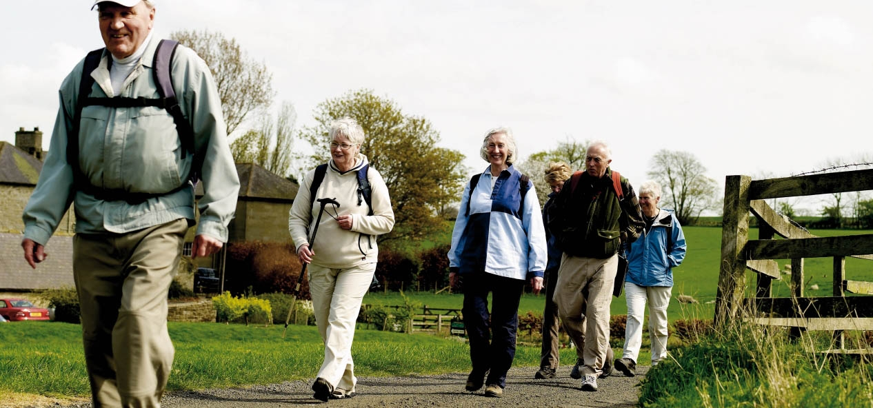 A group of older people walking in the countryside