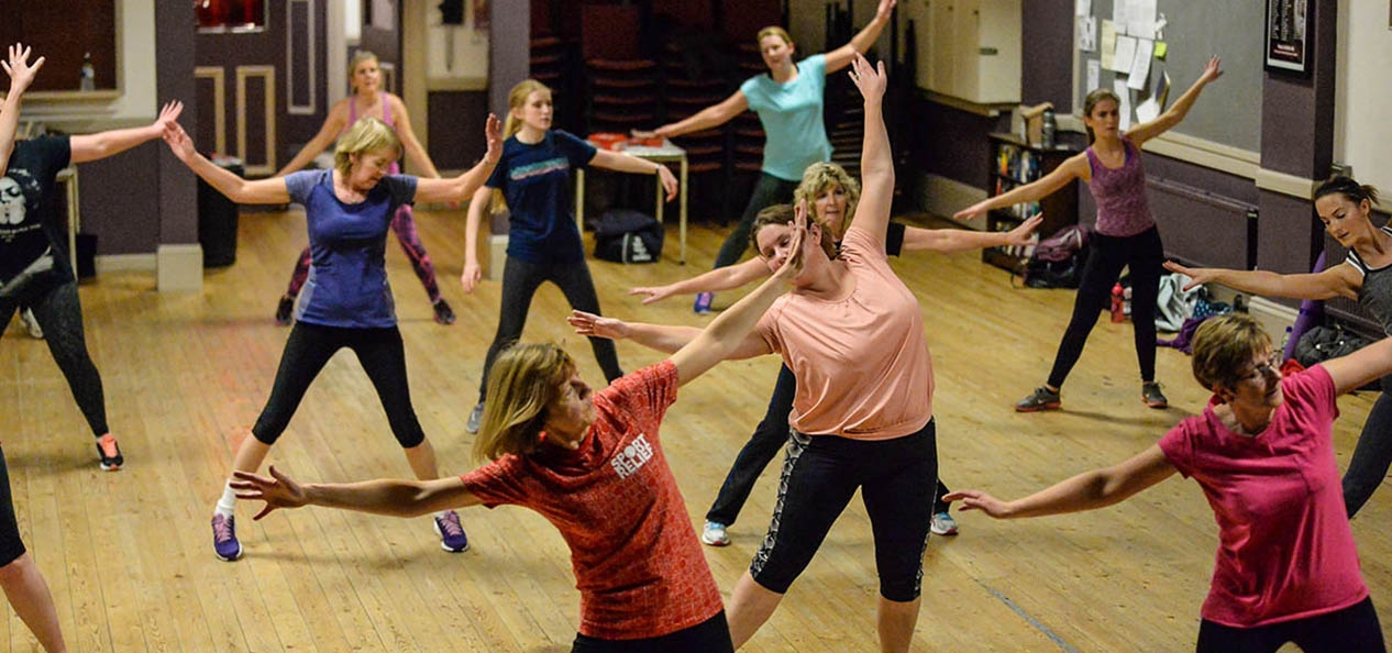 A group of women do an exercise class in a village hall