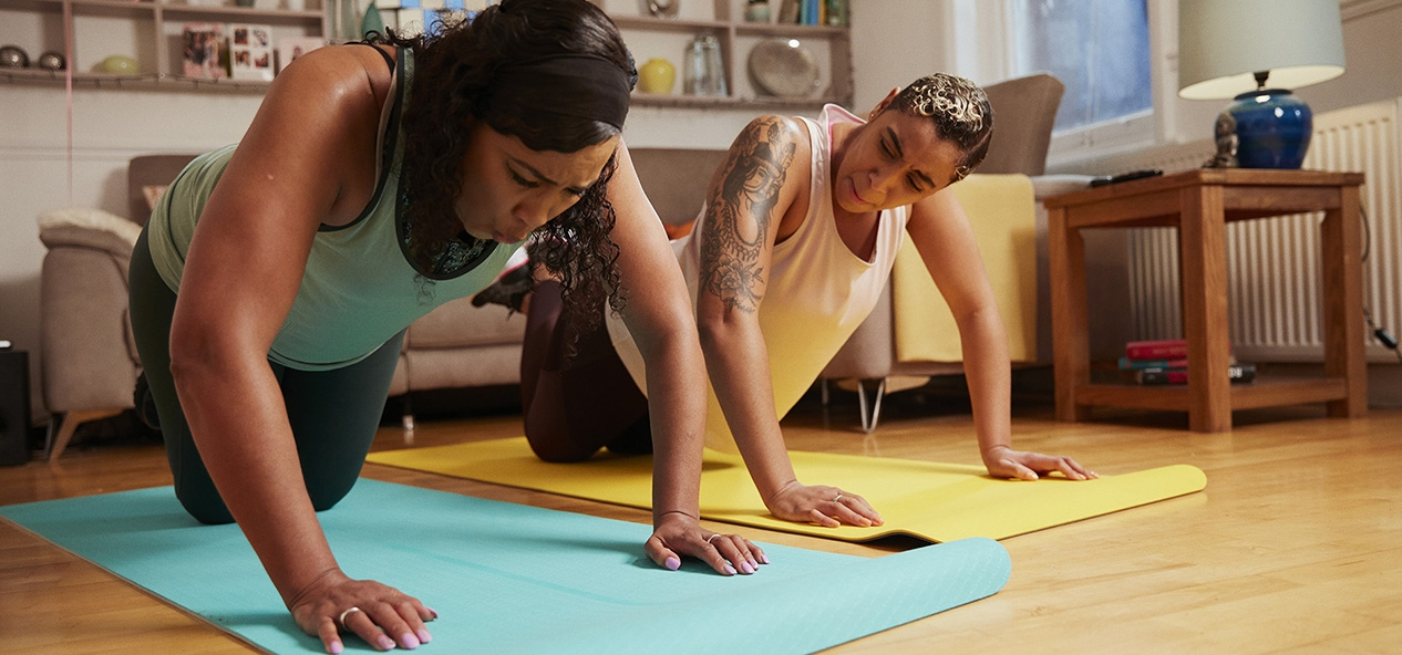 Two women do yoga at home in their living room