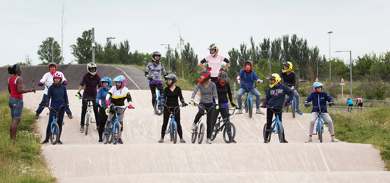A group of cyclists line up on a BMX track