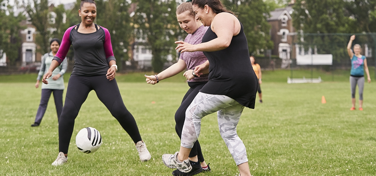 A group of women have a kickabout in a park