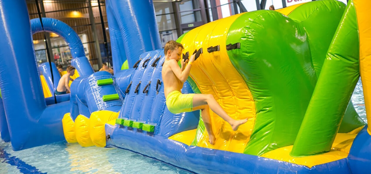 A boy plays on an inflatable obstacle course in a swimming pool